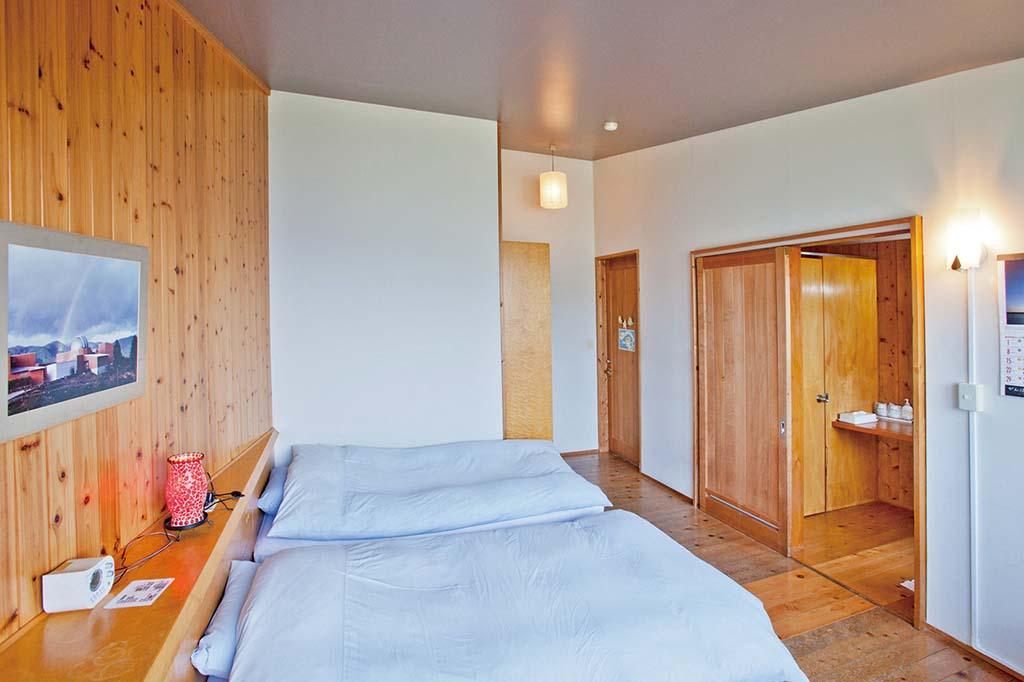 木の温もり感じるツインルーム。ロフトと2段ベッドがついたファミリールームもあり