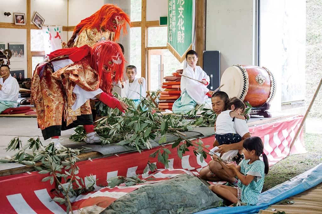 「柴曳」で観客の少女とアメノコヤネノミコトが榊を引っ張り合う